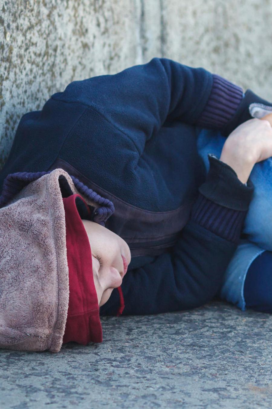 niño migrante duerme en la calle