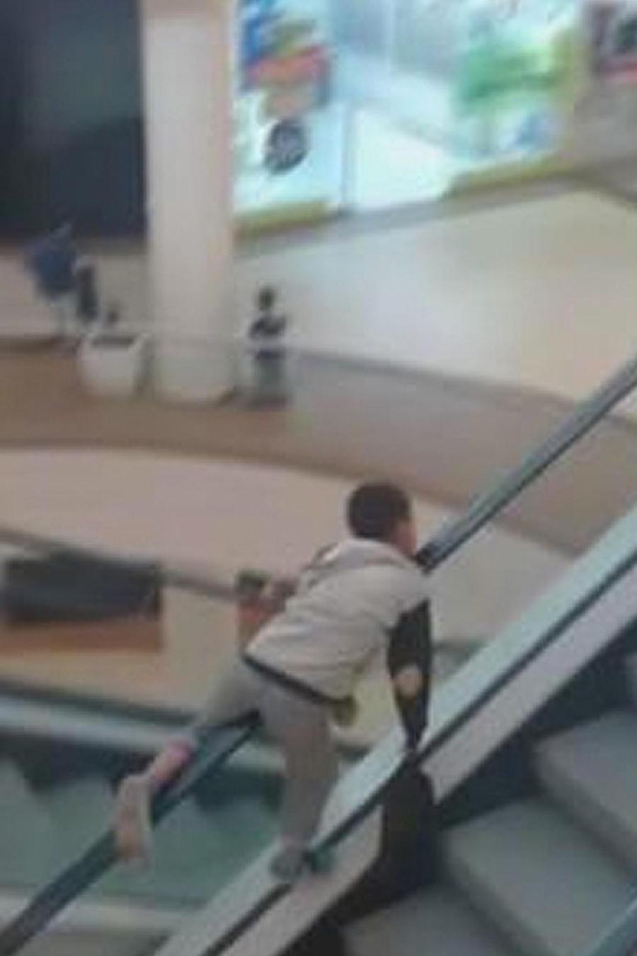 niño colgado de escalera electrica
