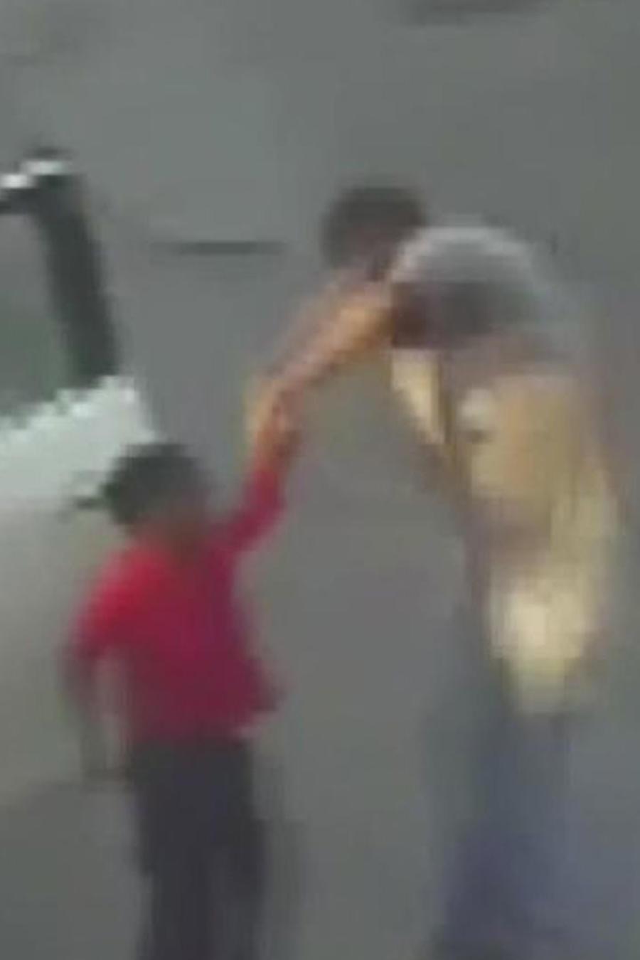 hombre azotando a niño