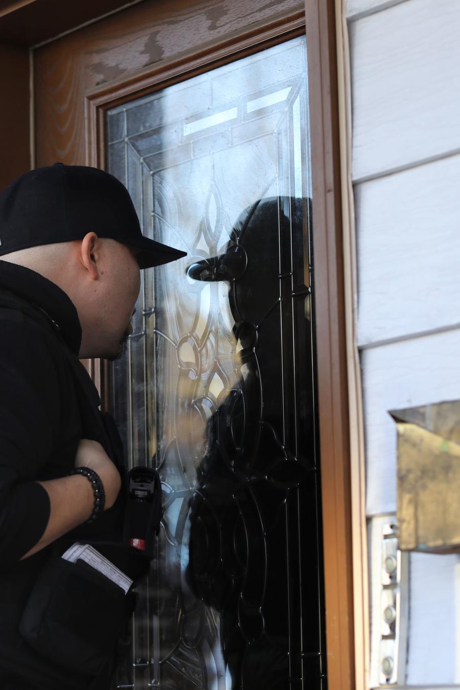Fotografía de archivo de un agente de ICE tocando a la puerta de un hogar
