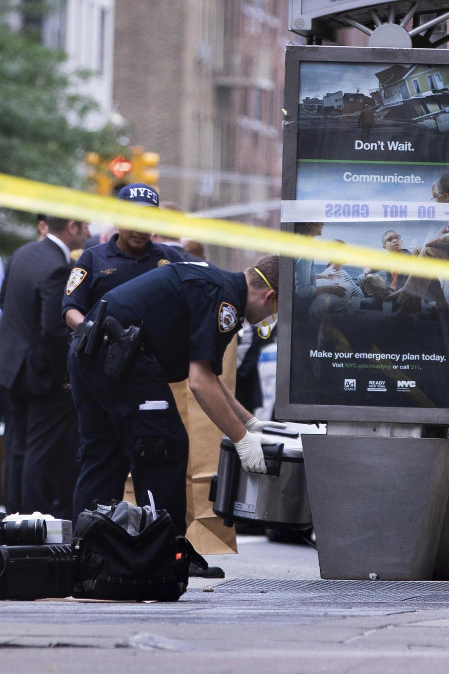 Un investigador de la policía recoge un paquete sospechoso este viernes afuera del metro de la Ciudad de Nueva York