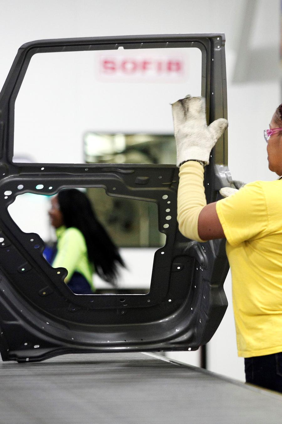 Un trabajador maneja una puerta que salió de la nueva prensa de $ 63 millones en la planta de estampado de automóviles Warren de Fiat Chrysler, Estados Unidos, Warren, Michigan