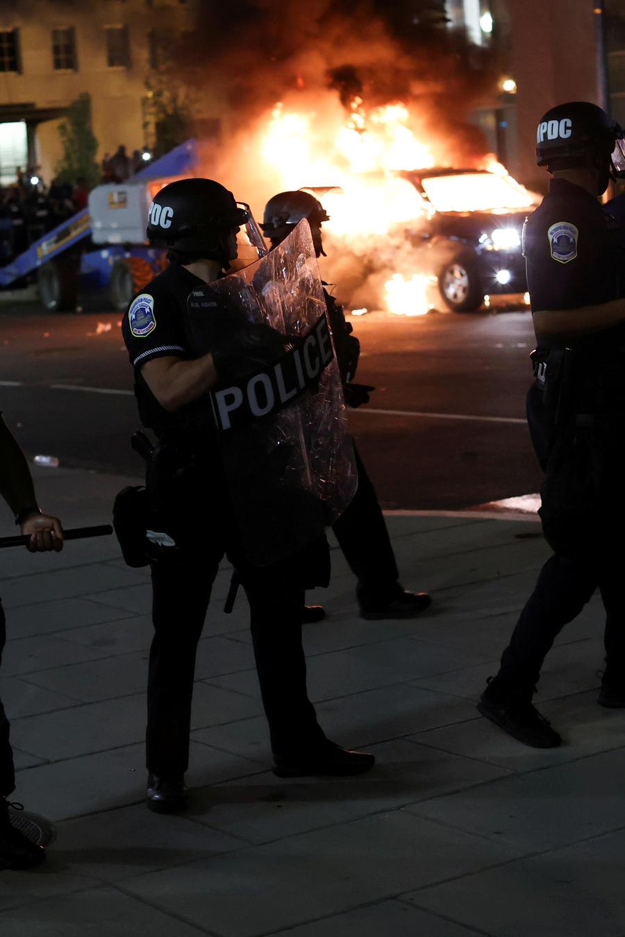 Los oficiales de policía observan cómo un automóvil arde en la parte posterior mientras los manifestantes continúan manifestando contra la muerte en la custodia policial de George Floyd, en Minneapolis, cerca de la Casa Blanca, en Washington, EE.UU.
