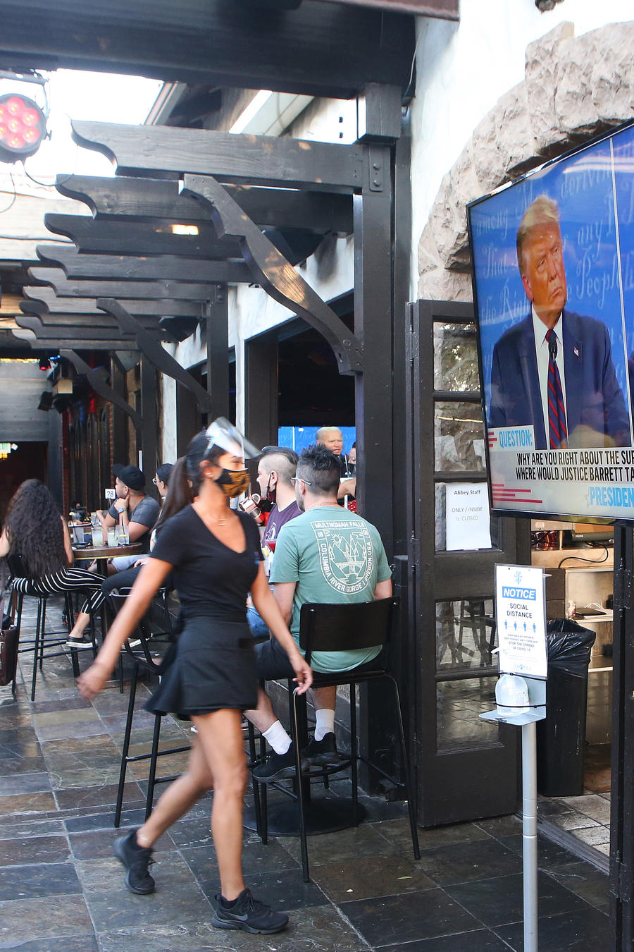 La gente se sienta y mira una transmisión del primer debate entre el presidente Donald Trump y el candidato presidencial demócrata Joe Biden en The Abbey con asientos al aire libre manteniendo la distancia social en West Hollywood, California.