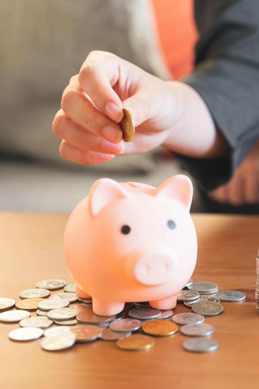 Mujer colocando dinero en la alcancía