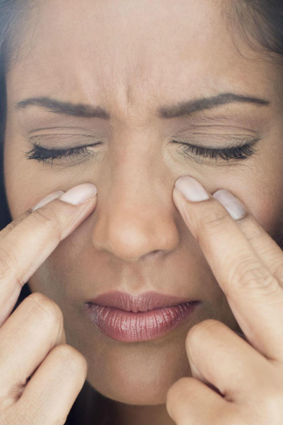 Mujer tocando el contorno de su nariz