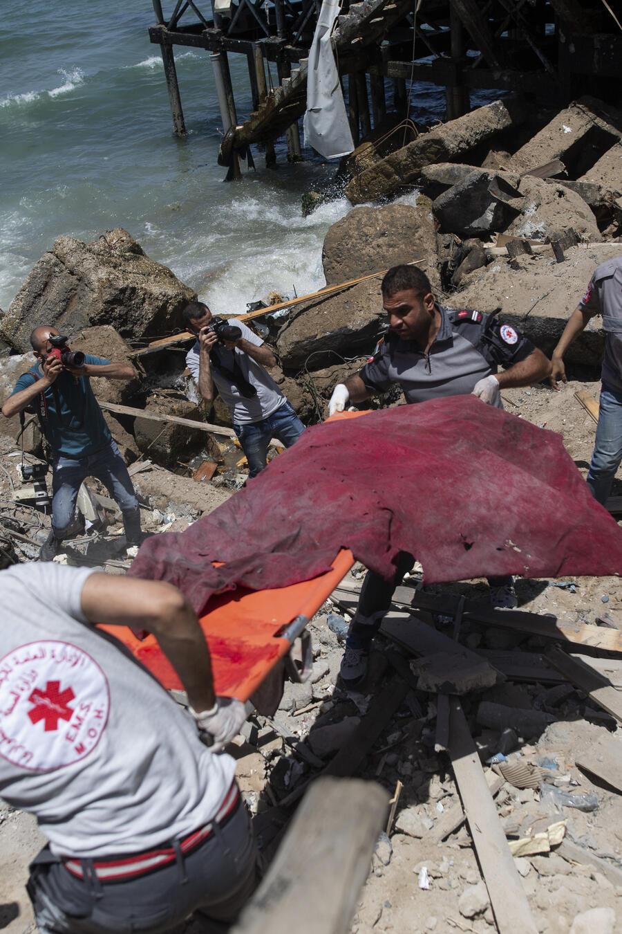 Rescatistas palestinos transportan los restos de un hombre en la ciudad de Gaza.