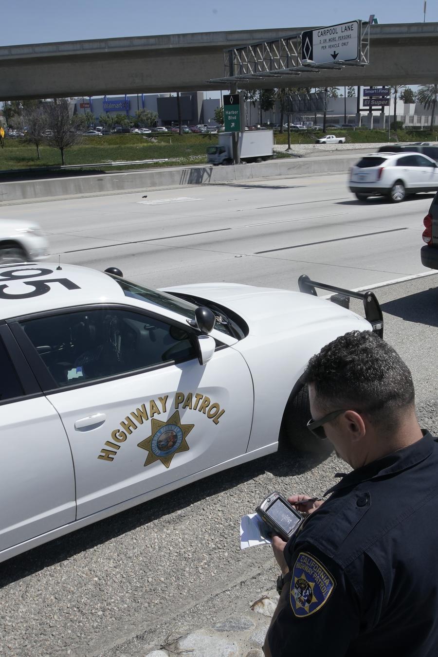 En esta imagen del 23 de abril de 2021, el oficial de la Patrulla de Caminos de California Troy Christensen revisa una licencia de conducir después de detener a un automovilista en la Interestatal 5 que conducía a exceso de velocidad en Anaheim, Californi