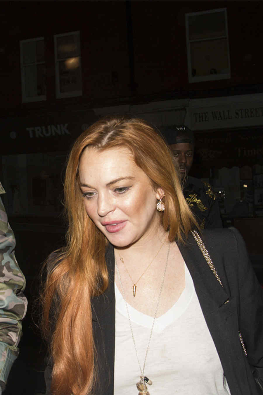Actress Lindsay Lohan looks cheerful as she arrives at Chiltern Firehouse with friends wearing a bra less white t-shirt in London