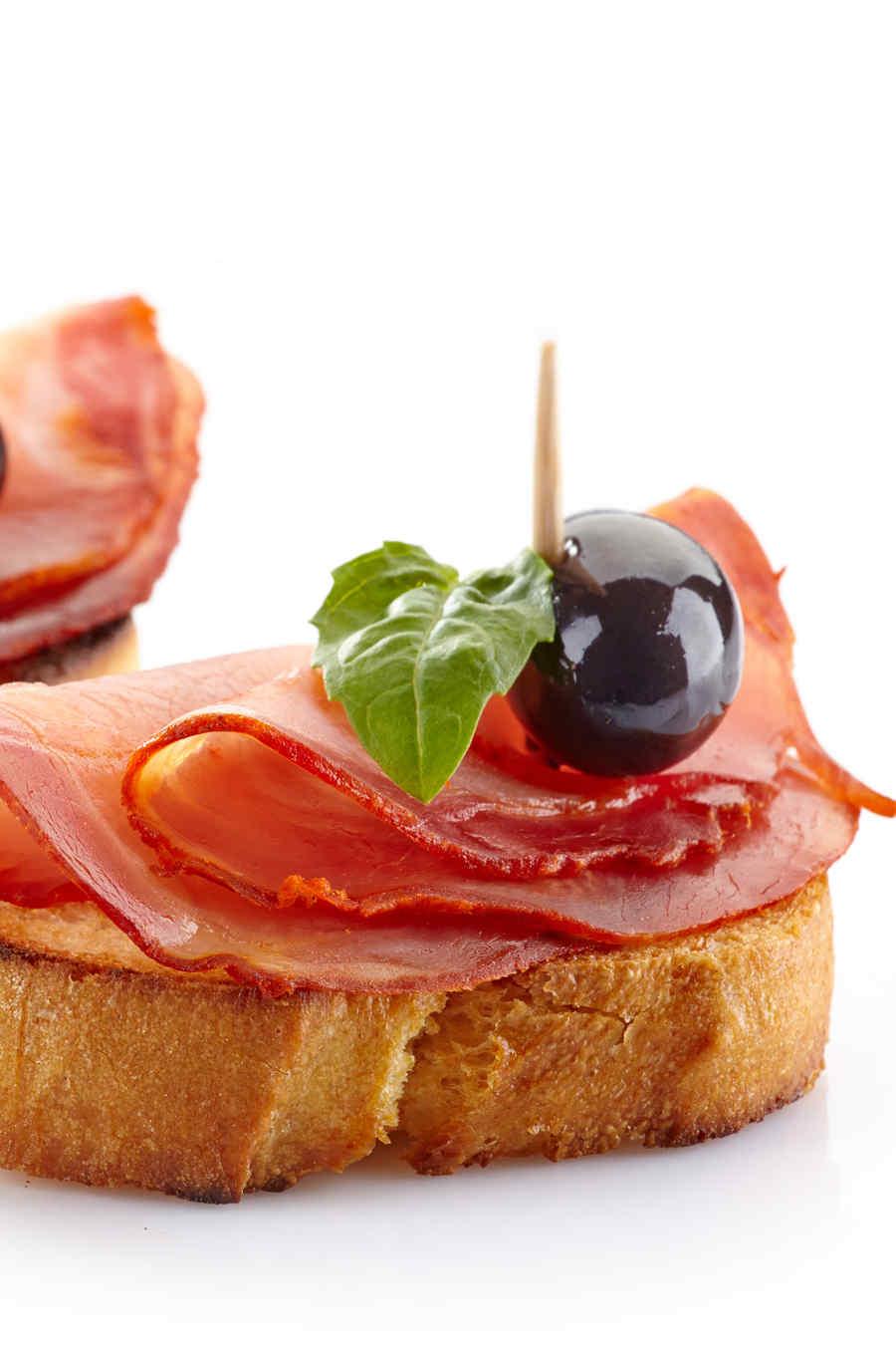 Tostada con jamón, aceitunas y albahaca