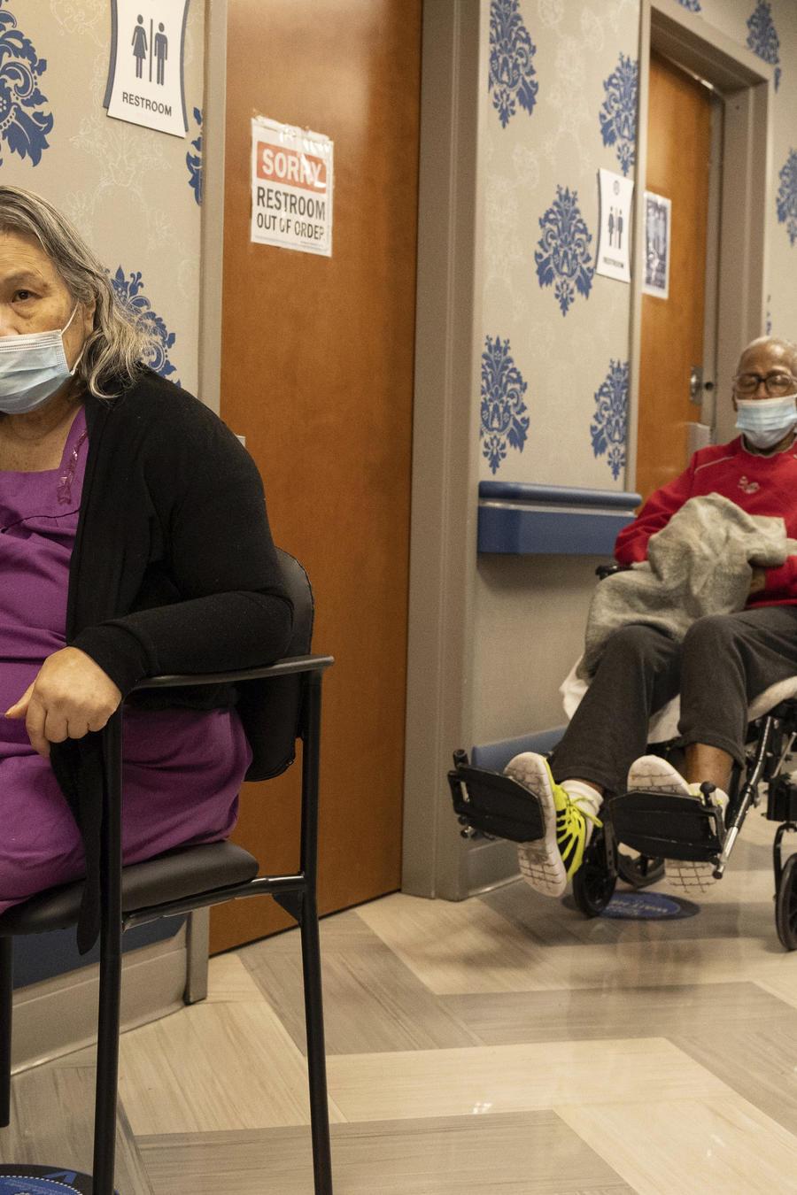 Residentes hacen una fila para ponerse la vacuna contra el COVID-19 en el Centro de Enfermería y Rehabilitación de Harlem.