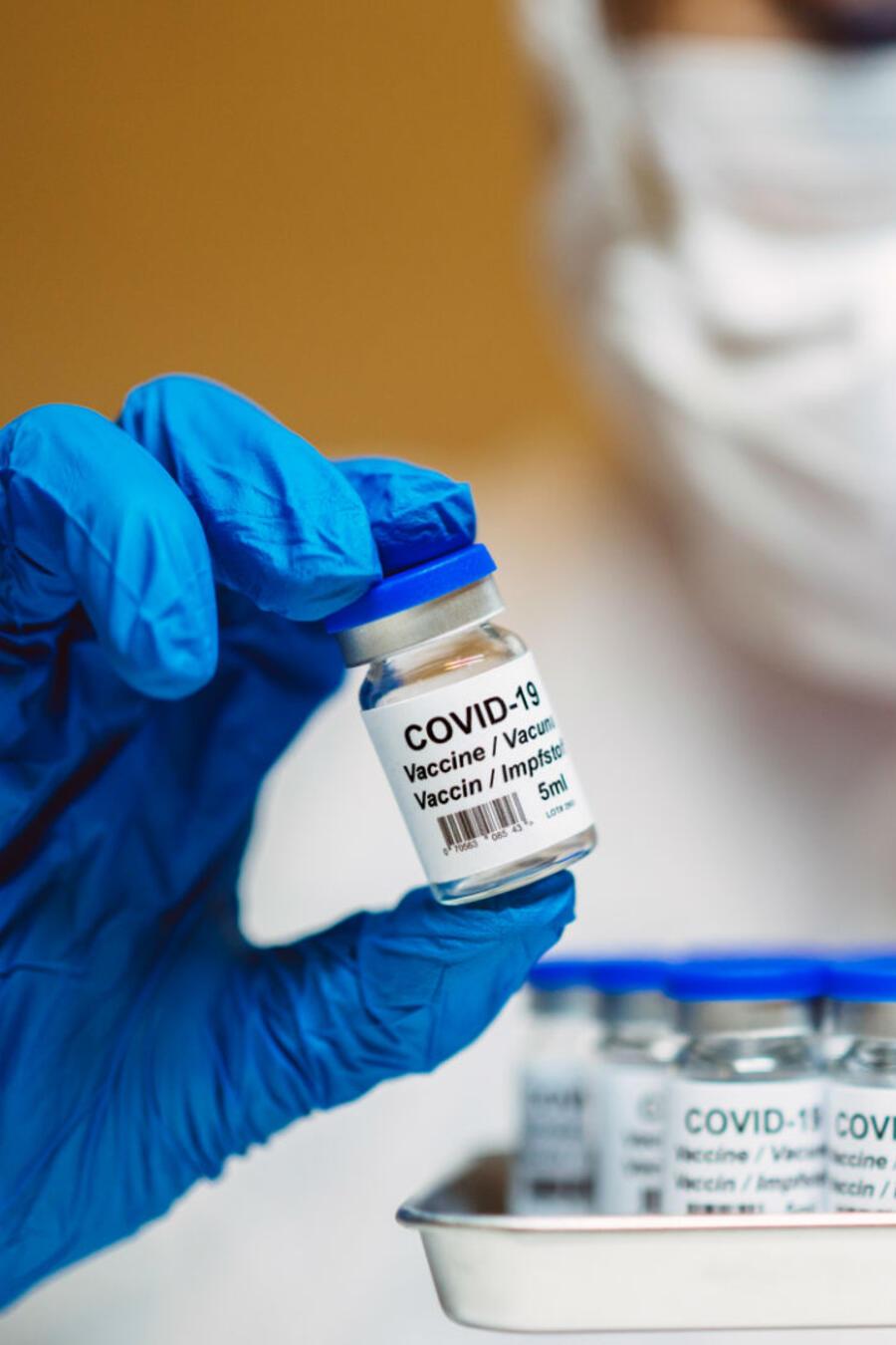 Doctora sosteniendo varias dosis de vacunas contra COVID-19