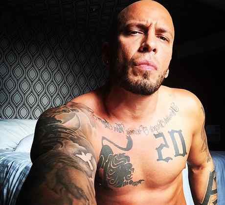 Alexis sin camisa mostrando sus tatuajes en un selfie.