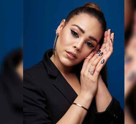 Danna Paola posando con las manos en su cara