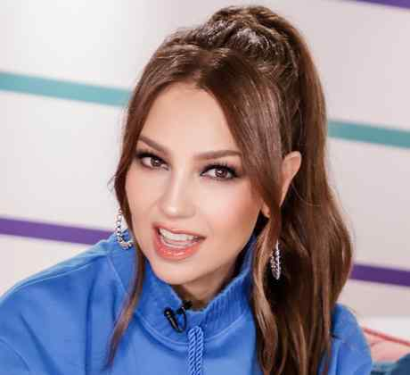 Thalia takes photo wearing a blue jacket