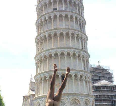 Hombre desnudo parado de manos frente a la Torre de Pisa