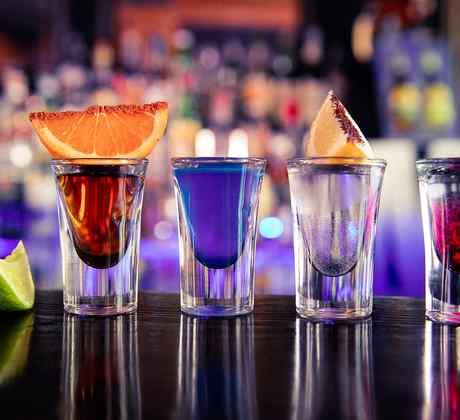 5 tequilas coloridos en la barra de un bar