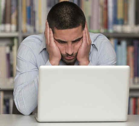 Hombre joven estudiando en la computadora