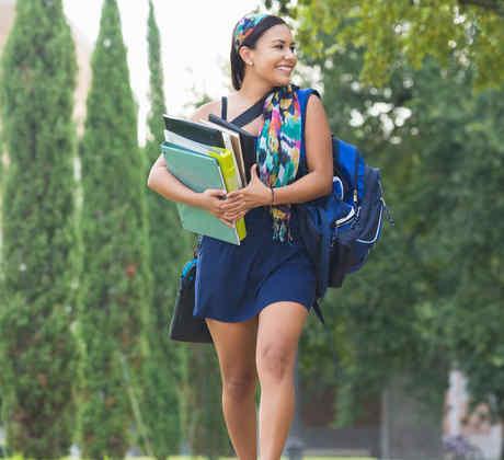 Muchacha caminando en universidad con cuadernos