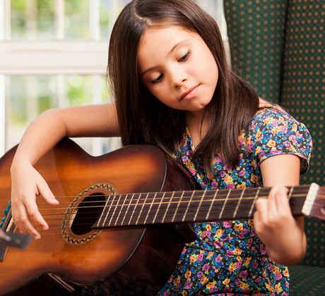 Niña hispana tocando la guitarra
