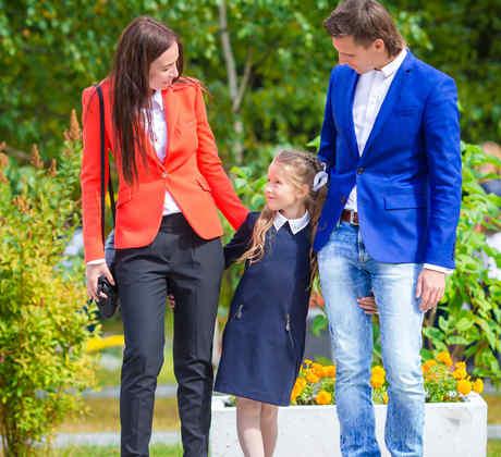 Padres llevando a niña a la escuela