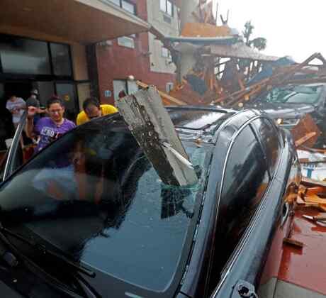 Una mujer revisa su vehículo tras el huracán Michael, después de que se derrumbara el toldo del hotel, en Panama City Beach, Florida, el miércoles 10 de octubre de 2018.