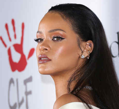 Rihanna de pie frente al logo de The Clara Lionel Foundation