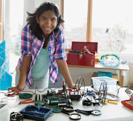 Niña de secundaria recargada en mesa con proyecto de tecnología
