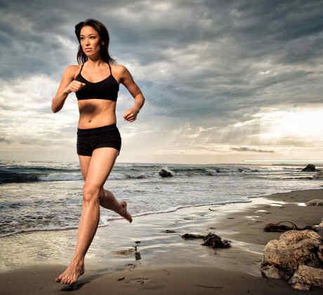 Mujer joven corriendo descalza en la playa