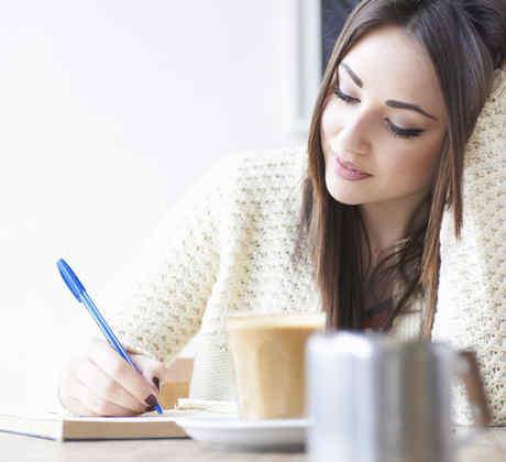 Mujer joven escribiendo y bebiendo café