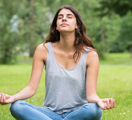Mujer meditando en un parque