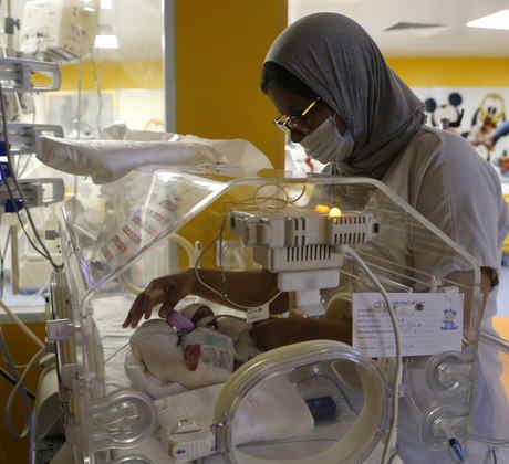 Una enfermera marroquí cuida a uno de los nueve bebés protegidos en una incubadora en la sala de maternidad de la clínica privada de Ain Borja en Casablanca, Marruecos, el miércoles 5 de mayo de 2021.