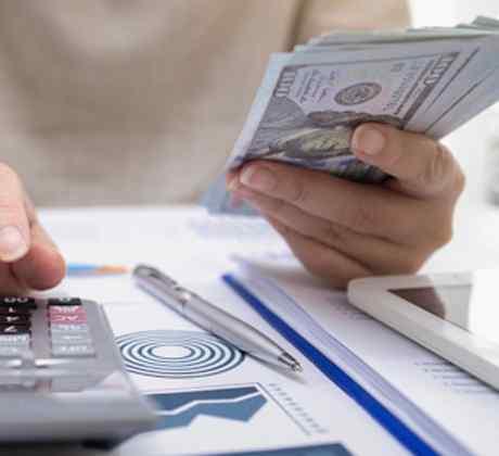 Mujer usando la calculadora y sosteniendo unos dólares