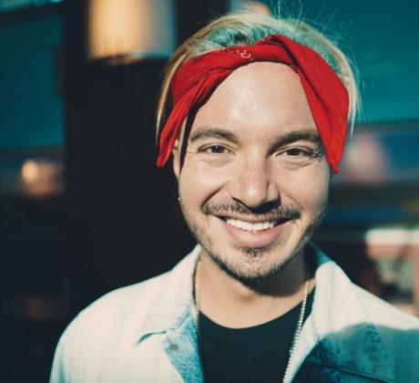 J Balvin sonriendo con nudo rojo en la cabeza
