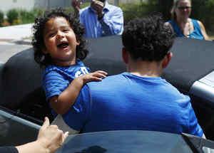 Un niño que había sido separado de su padre sonríe al ser reunido de nuevo con él