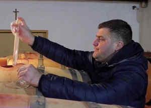 Hombres sacando vino de un barril