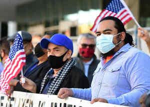 Activistas pro inmigrantes ondean banderas frente a edificio federal en Los Angeles
