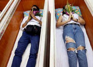 Personas en ritual con ataúdes en Bangkok