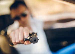 Hombre apunta arma desde un auto