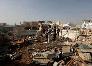 La gente se para en el techo de una casa en medio de los escombros de un avión de pasajeros, se estrelló en una zona residencial cerca de un aeropuerto en Karachi, Pakistán