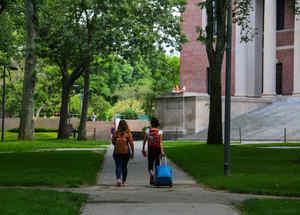 Se ve a dos estudiantes saliendo de su campus con equipaje en las instalaciones de la Universidad de Harvard en Cambridge