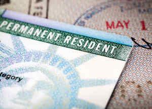 Una tarjeta verde sobre un pasaporte abierto, primer plano.